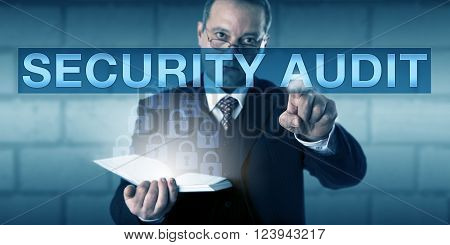 Corporate auditor is touching the term SECURITY AUDIT on a transparent screen. The man is looking across his spectacles with a concentrated expression. Business and information technology concept.