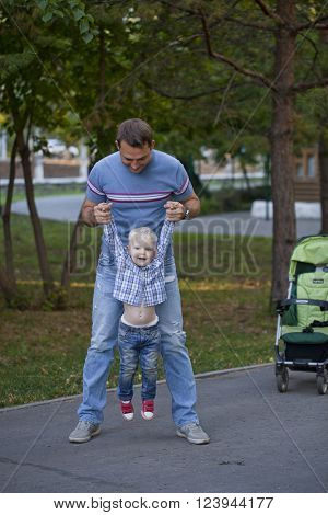 Young Father with two year old son in summer park