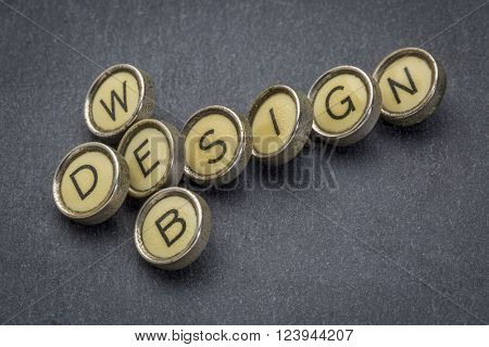 web design banner in old round typewriter keys against gray slate stone