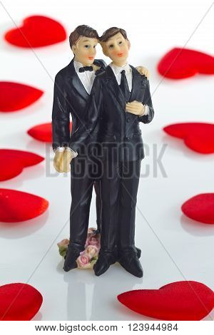 Gay wedding Cake Figurine with little velvet hearts as Background.