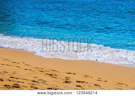 Yellow sandy beach and blue sea with waves and seafoam. Background image for travel, summer vacation, and recreation. Vivid photo of tropical paradise.