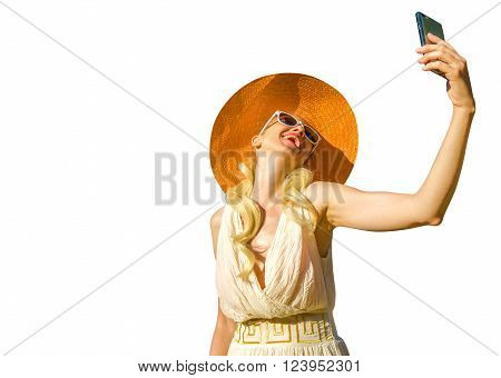 A smiling and fashionable model with an orange wide-brimmed hat and dressed in Greek style, takes a selfie. Isolated on white background.