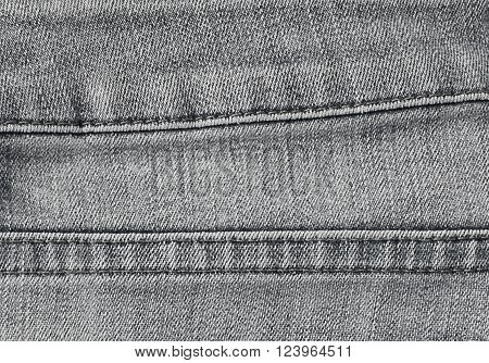 Fabric Texture Close Up of Black Denim Jean Texture with The Stitched Seams.