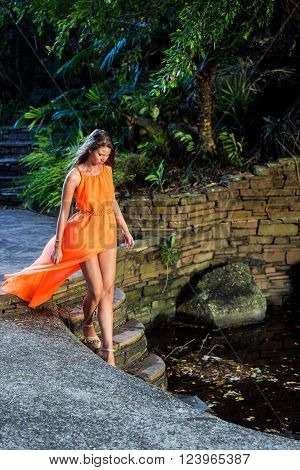 Young woman in orange dress walking down on stairs in the tropical park
