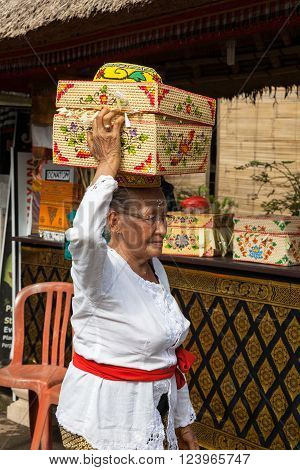 UBUD, INDONESIA - MARCH 2: Senior woman with basket on the head during the celebration before Nyepi (Balinese Day of Silence) on March 2, 2016 in Ubud, Indonesia.