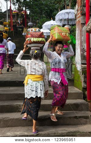 UBUD, INDONESIA - MARCH 2: Women with baskets on the heads during the celebration before Nyepi (Balinese Day of Silence) on March 2, 2016 in Ubud, Indonesia.