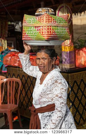 UBUD INDONESIA - MARCH 2: Senior woman with basket on the head during the celebration before Nyepi (Balinese Day of Silence) on March 2 2016 in Ubud Indonesia.