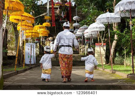 UBUD, INDONESIA - MARCH 2: Man with children walks up the stairs during the celebration before Nyepi (Balinese Day of Silence) on March 2, 2016 in Ubud, Indonesia.