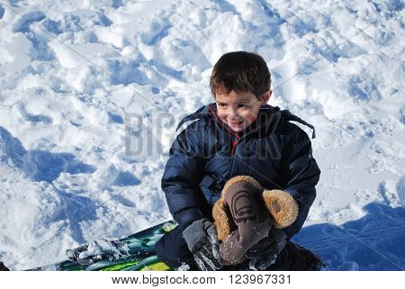 Little boy in ski clothes and toboggan playing in the snow ready to have a snowball fight.