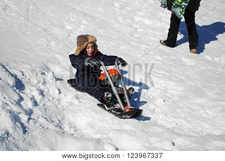 Little boy in ski clothes and toboggan playing in the snow sledding on a motorcycle.