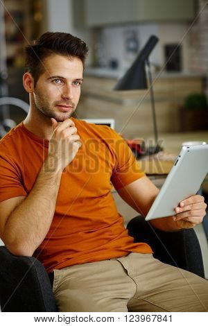 Thoughtful young man using tablet computer.
