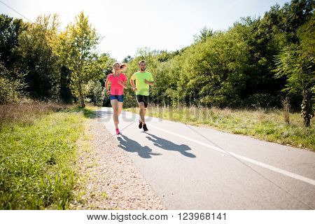 Young couple running together in summer sunny nature