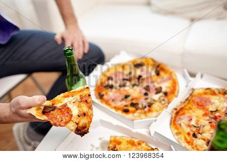 friendship, alcohol, people, celebration and holidays concept - close up of man drinking beer and eating pizza at home