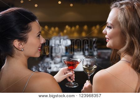 celebration, friends, bachelorette party and holidays concept - happy women drinking wine and cocktail at night club bar