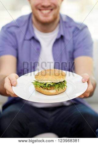 fast food, unhealthy eating, people and junk-food - close up of happy man holding hamburger on plate at home