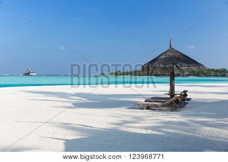 travel, tourism, vacation and summer holidays concept - palapa and sunbeds over sea and sky on maldives beach