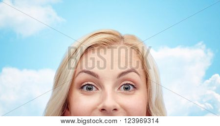 curiosity, advertisement and people concept - happy young woman or teenage girl face over blue sky and clouds background