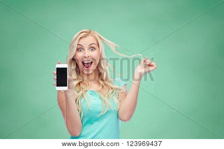 emotions, expressions, education, technology and people concept - smiling young woman or teenage girl showing blank smartphone screen over green school chalk board background