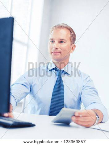 business, office, tax, school and education concept - smiling businessman with calculator, computer and papers
