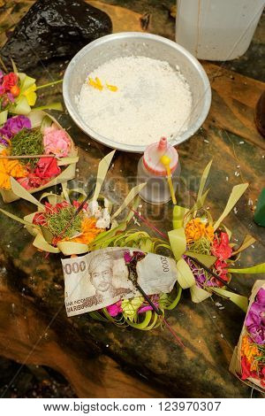 A stick of incense burns through an Indonesian banknote among Balinese-Hindu offerings of flower petals rice holy water and money on an altar at a Hindu temple at Sebatu Sacred Springs in Bali Indonesia.