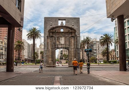 Montevideo, Uruguay - December 15, 2012: People walking on Sarandi pedestrian street, in the Ciudad Vieja area with the landmark Puerta de la Ciudadela (Citadel Gate) in the center.