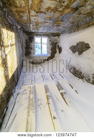Room in an abandoned building swept snow.