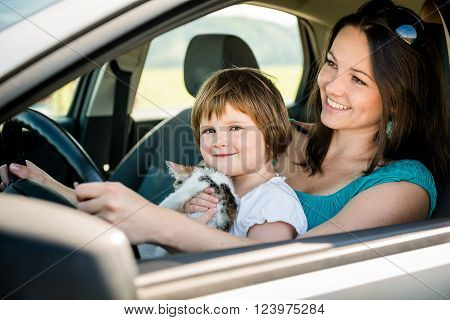 Mother and child holding kitten pretend driving car sitting all on front driver seat