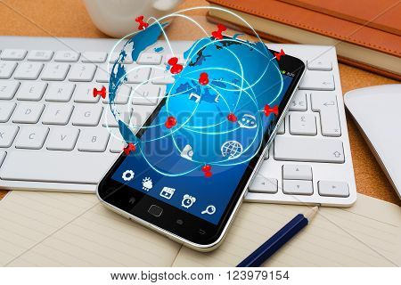 Modern mobile phone in office with travel icon application flying over