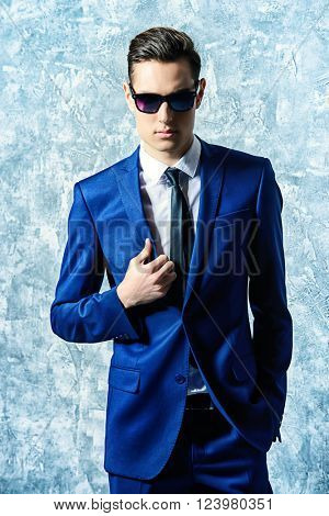 Fashion shot of a handsome young man in elegant classic suit and sunglasses.