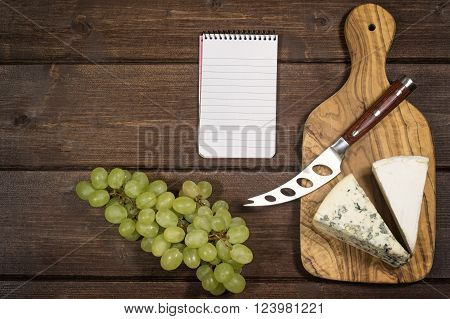 Two kinds of cheese and stainless steel cheese knife with wood handle are is lying on the board of olive wood. Grapes and paper notebook are lying on a wooden board.