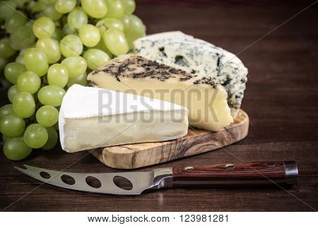 Three kinds of cheese and grapes of the white wine are lying on the board of olive wood. Stainless steel cheese knife is lying on a wooden board in foreground. Photo is edited as an vintage with dark edges.
