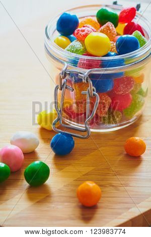 Colorful candies and jujube in jar on the wooden table