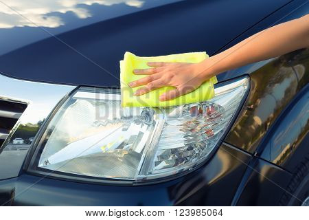Girl's hand wiping cloth on car's headlight.