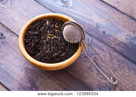 Dried tea leaves in bamboo bowl and tea strainer on wooden background. Copy space