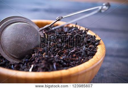 Dried tea leaves in bamboo bowl and tea strainer on wooden background. Close up