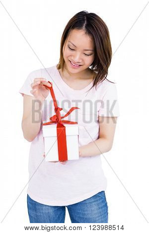 Young woman opening a present on white background
