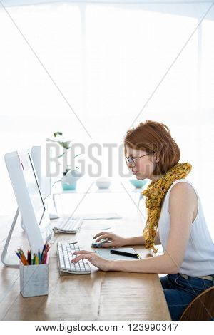 thoughtful hipster businesswoman, sitting at her desk, concentrating on her computer