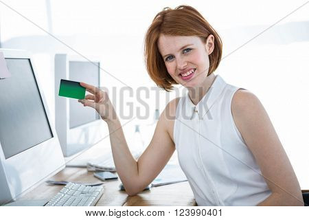 smiling hipster business woman sitting at her desk, holding a credit card
