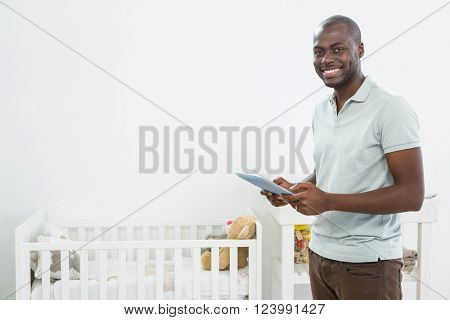 Smiling man standing next to a cradle and smiling while using a digital tablet at home