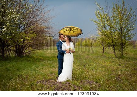 Happy Bride and groom on their wedding day with rainy sky