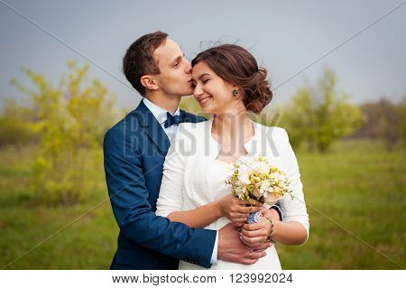 Bride and groom walking on the river smiling and kissing