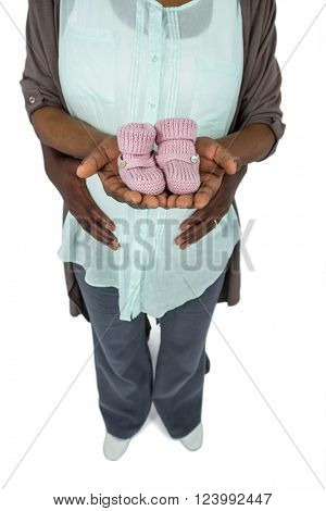 Pregnant couple holding baby shoes on white background