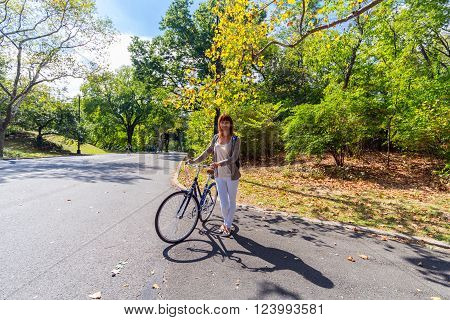 young woman with a bicycle in the Central park, New York, USA