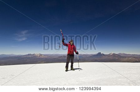 man in red jacket with ice-axe and backpack standing on ice top of Sajama Volcano in Bolivia, 6542m