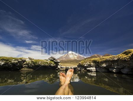 Feet in hot springs near snow-covered volcano Sajama in Bolivia with bushes of grass