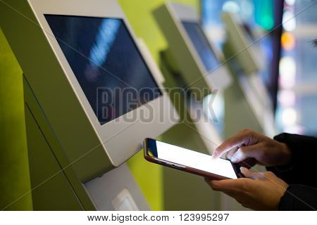 Woman using mobile phone for paying on vending system