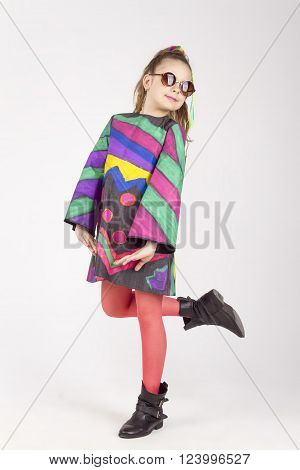 the portrait of the cheerful naughty little girl poses in a camera