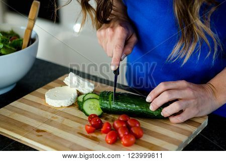 woman slicing vegetables on a wooden chopping board
