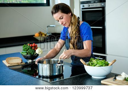 smiling woman preparing vegetables for dinner on a hob
