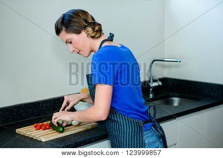 Happy woman preparing some vegetables in the kitchen